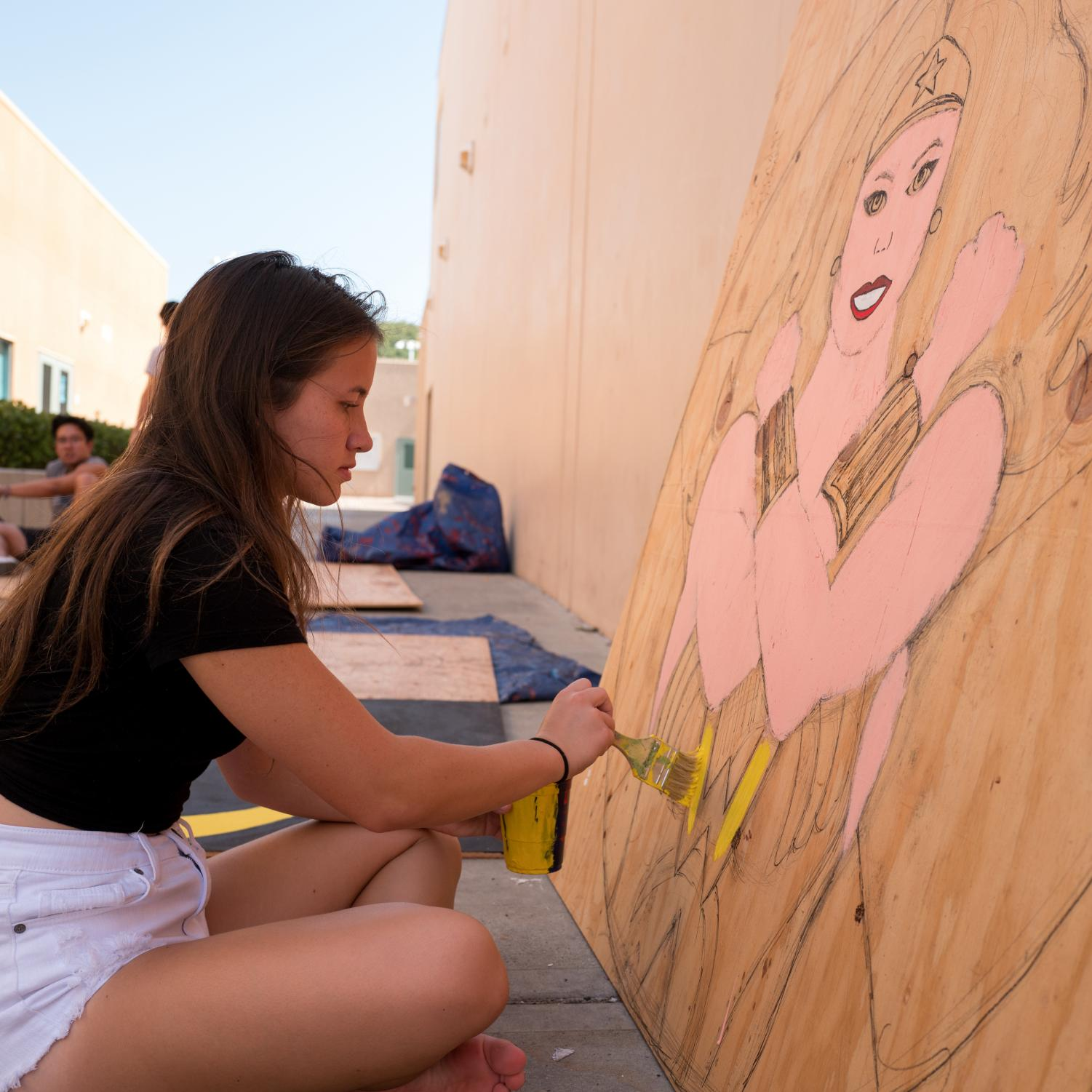 PAINTING THE UNIVERSE: Senior Ashley Peters brings a Wonder Woman decoration to life with vivid colors and bold brushstrokes in anticipation of the upcoming Homecoming dance on Oct. 5.