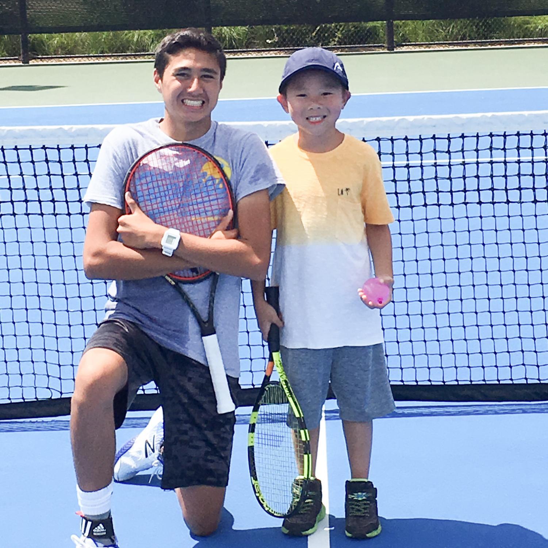 HOT SUMMER SUN: Senior Nabil Fawaz helps young players hone their tennis skills.