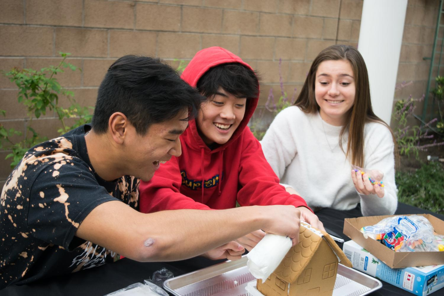 OH SNAP!: Juniors Audrey Prickett, Andrew Kim and Evan Choi (left to right) decorate the roof of their gingerbread house with icing and colorful candies.