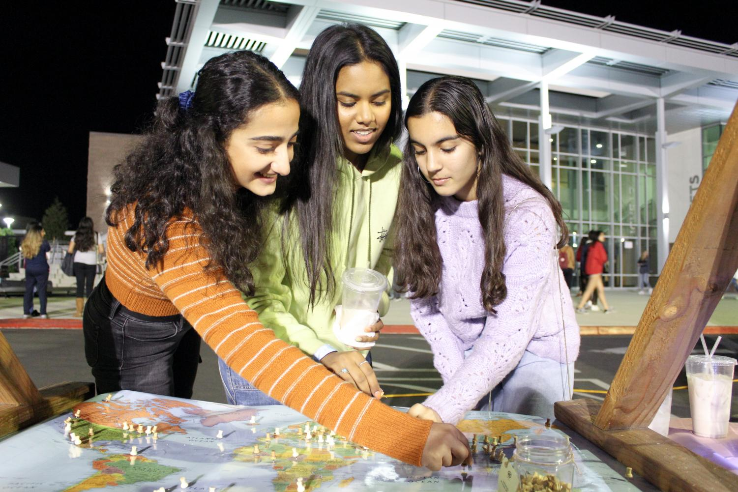 ORIGINS: Seniors Saghar Rafie, Akshita Agirishetti and Nelly Safi plot a point on the map to represent the place they are from.