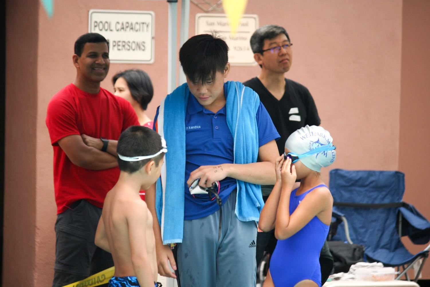 HUDDLE UP: Junior Kendrick Pham shares his expertise with a couple of young swimmers.