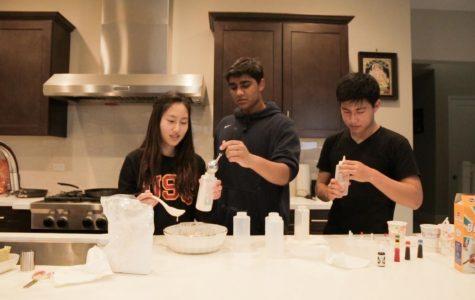 (FLOUR)ISHING ARTISTS: Juniors Erin Kim, Varun Vishnubhotla, and Anlon Zhu (left to right) fill squirt bottles with colored pancake batter.