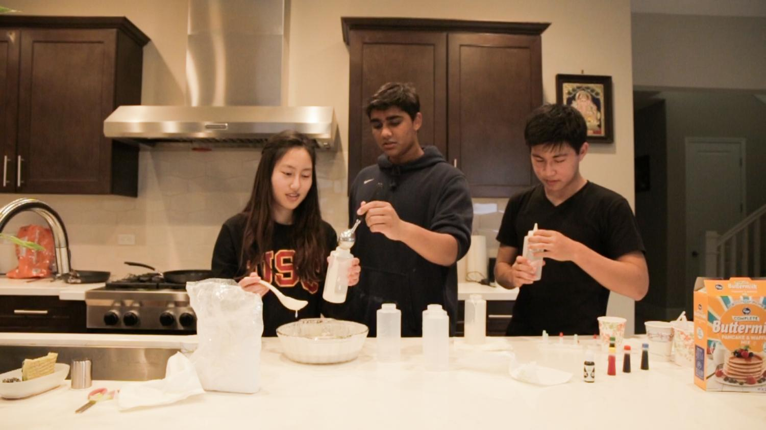 (FLOUR)ISHING ARTISTS: Juniors Erin Kim, Varun Vishnubhotla, and Anlon Zhu (left to right) fill squirt bottles with colored pancake batter.