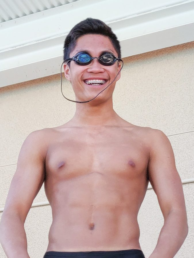 TWO WALKS OF LIFE: Junior Benjamin Liu prepares to get into the pool before swim practice.