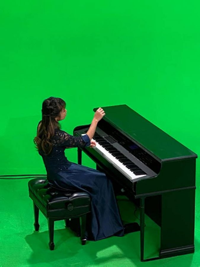 "IN HER FORTE: Senior Bethany Huang films her accompanying performance to ""The Star-Spangled Banner."""