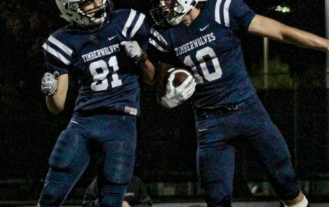 PLAYING WITH PASSION: Juniors Travis Arena and Ali Alas- seel engage in a post-touchdown celebration, showing team spirit.