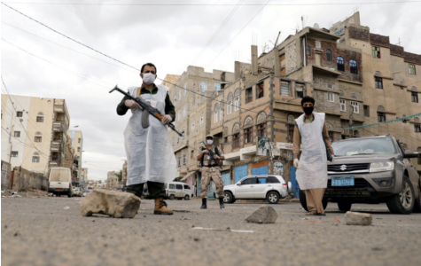 A WAR ON TWO FRONTS: Armed men wear masks to patrol the streets of Sanaa, Yemen, during a 24-hour curfew, as concerns regarding COVID-19 grow.
