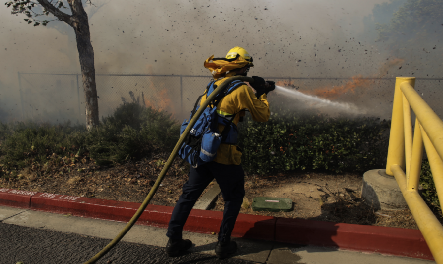 AN EMPTY SCHOOL: Smoke billows over Northwood as a firefighter combats the wind-fueled Silverado fire, which burned through the edges of the Northwood campus and the surrounding vegetation.