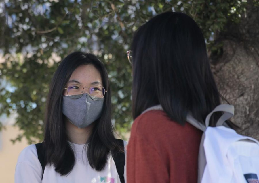 SAYING HI TO HYBRID: Seniors Claire Wang and Emily Yu wear face masks as they socially distance by The Oak during break.
