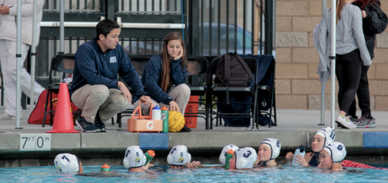 STOKED WHILE SOAKED: Head Coach Kyle Kim-E and Assistant Coach Is- abelle Comtois review the team's playbook during a routine water break.