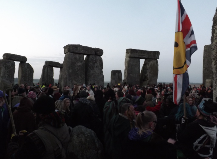 A mix of attendees in robes and casual wear gathering at Stonehenge on the 2015 March equinox.