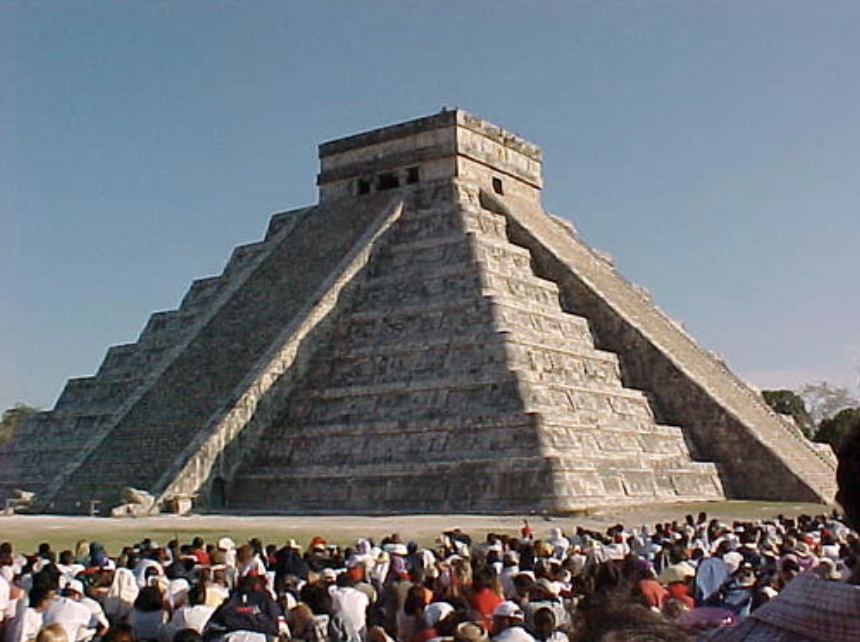 The Chichen Itza pyramid in the late afternoon, with a crowd watching the serpent shadow illusion.