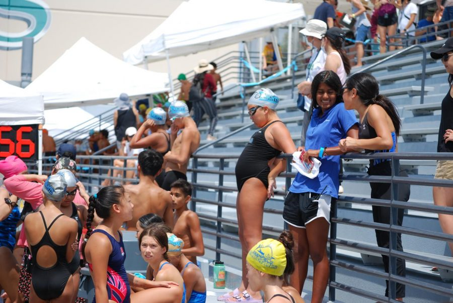 CONSTRUCTIVE COACHING: Senior Simran Patel offers helpful advice and support to a swimmer before her race.
